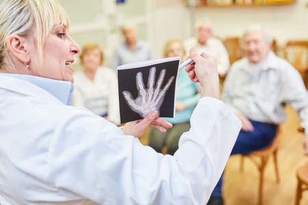 Woman as a doctor gives a presentation on health advice for senior citizens in a retirement home