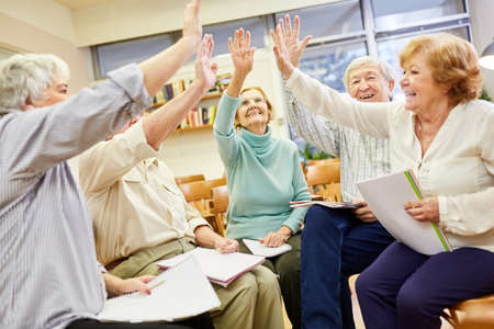 Group of vital seniors does high five exercise for interaction and cohesion