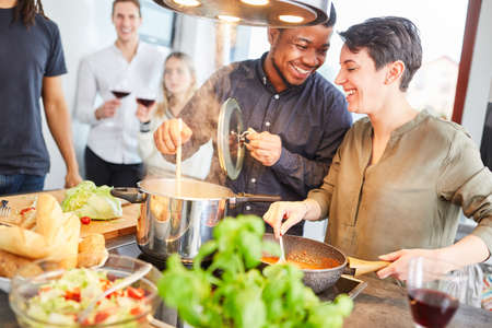 Friends cook pasta with tomato sauce in shared kitchen together for meal together Stock Photo