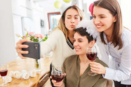 Women make selfie with bride at hen party at home with a glass of red wine Foto de archivo