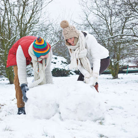 Man and woman build a snowman together in winter Archivio Fotografico