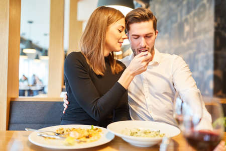 Young woman in love feeds her boyfriend at the restaurant rendezvous