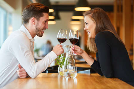 Amorous young couple having a rendezvous at the restaurant drinking a glass of red wine