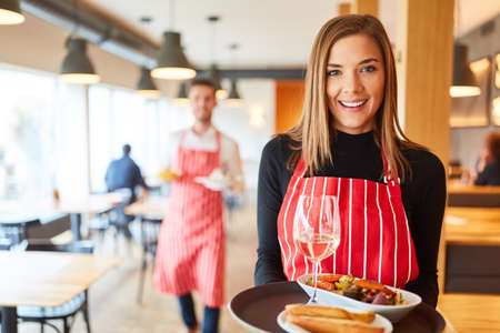 Young smiling woman serving as a waitress serves appetizers in the restaurant or bistro Archivio Fotografico