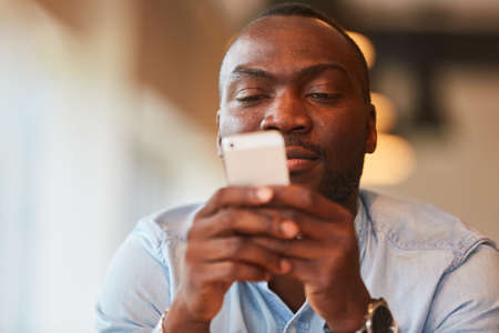 Young African man with smartphone app reads or writes an SMS