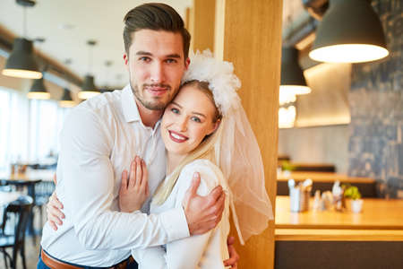 Young man hugs his girlfriend with bridal veil in the restaurant or bistro