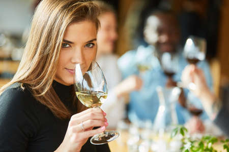 Young woman with friends at a wine tasting or tasting smells by the glass