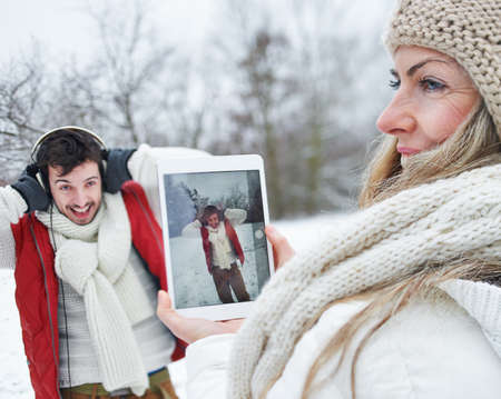 Laughing couple in winter takes photos together with tablet PC