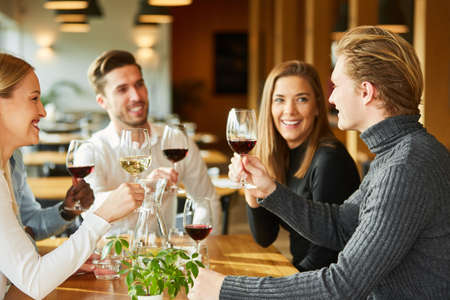 Friends celebrate together and have a glass of wine in the restaurant or bar Archivio Fotografico