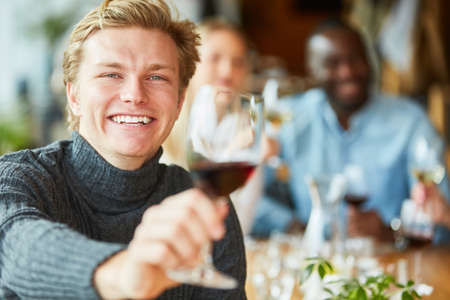 Cheerful young man tasting with a glass of red wine in the pub