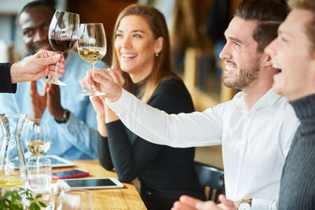 Friends toasting with glass of wine in restaurant at birthday party