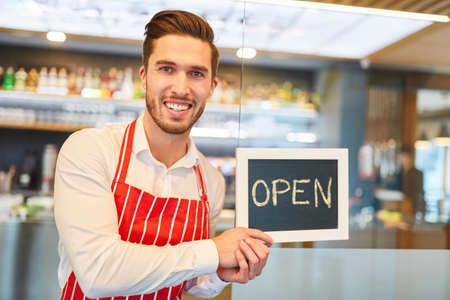 Waiter or restaurant founder holds an open chalkboard as a marketing Archivio Fotografico