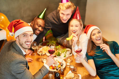 Young people at a Christmas party celebrate funny and happy with a lot of red wine