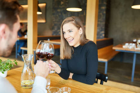 Young couple is drinking wine together while having a rendezvous in a restaurant Archivio Fotografico