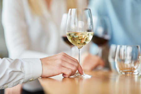 Hand with glass of white wine in a bistro or restaurant or bar