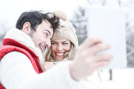 Laughing couple makes self-portraits with tablet computer in winter
