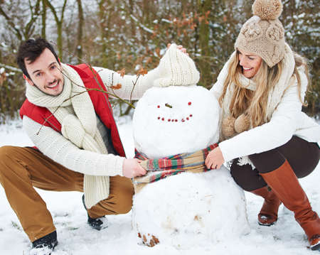 Laughing couple builds a snowman in the snow in winter Archivio Fotografico