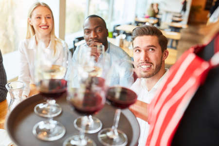 Group of guests in the restaurant or bistro are served by a waitress