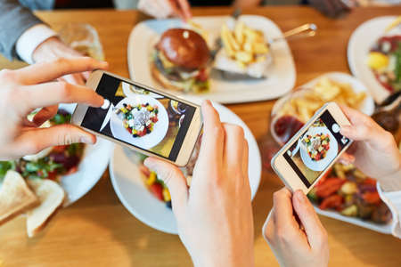 Hands with smartphones photograph food on table in restaurant