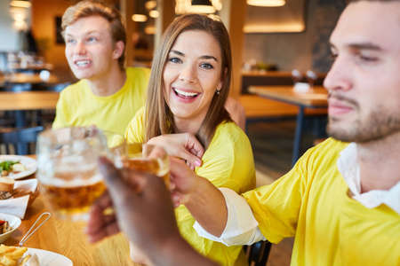 Friends as fans of a team while celebrating and drinking beer in a pub