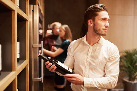 Young man with a bottle of red wine in front of a shelf in a wine shop