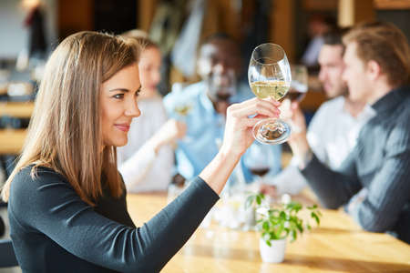 Young woman at a wine seminar tasting with a glass of white wine Archivio Fotografico