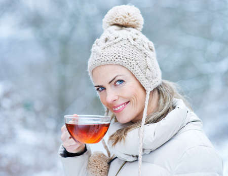 Smiling woman drinks a cup of black tea in winter Archivio Fotografico