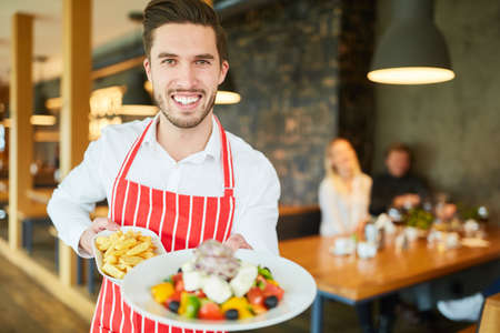 Young waiter serving in restaurant as greek salad with feta appetizer Archivio Fotografico