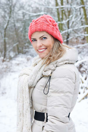 Smiling woman goes for a walk in the forest in winter Archivio Fotografico