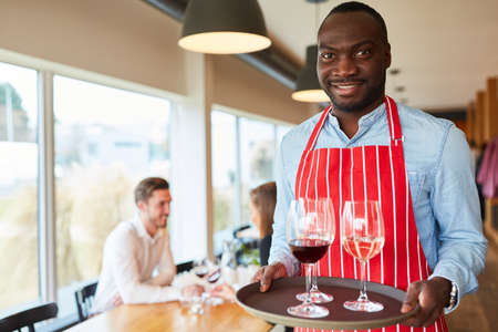African man as a waiter serving glasses with wine on a tray Archivio Fotografico