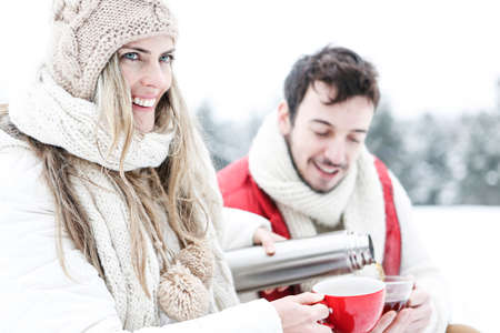 Happy couple drinking tea on the go in the snow in winter