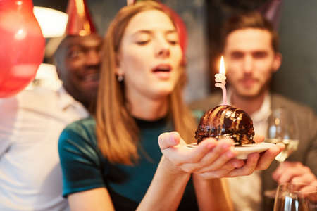 Woman while blowing out the candle on the birthday cake on a celebration