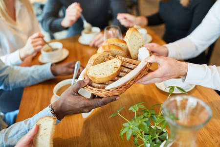 Hands distribute bread to soup while having lunch or dinner together
