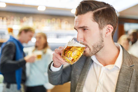 Young man is drinking a glass of beer in a pub or pub Archivio Fotografico