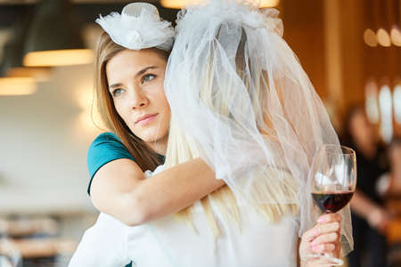 Melancholy woman hugs bride with bridal veil at hen party