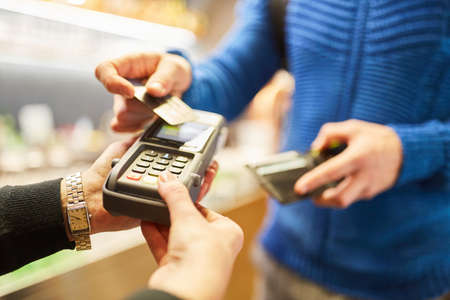 Cashless payment via NFC with credit card at the card terminal in retail Archivio Fotografico