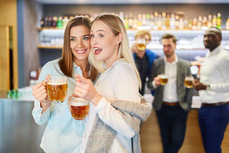 Two cheerful friends drink beer together in a pub after work