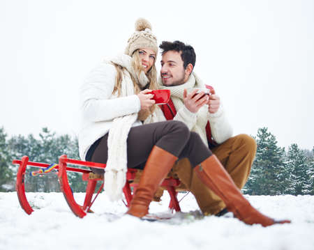 Smiling couple in winter drinks tea on a sled in the snow