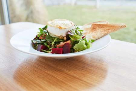 Fresh beetroot salad with camembert as a vegetarian appetizer in the bistro