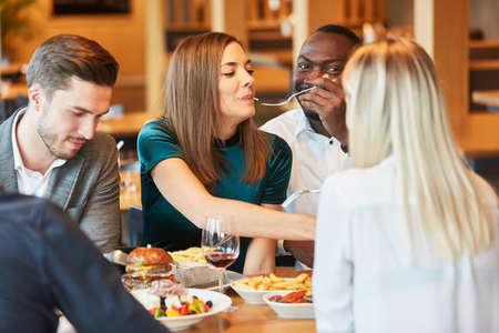 Group of friends having lunch together in a restaurant or bistro
