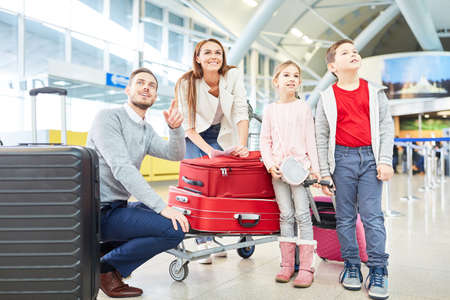Happy family with children is looking forward to the flight on vacation in the airport terminal
