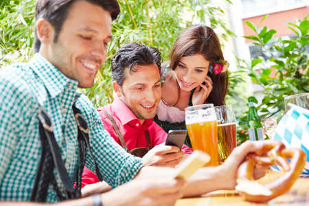 Friends surf the internet with smartphone in the beer garden in Bavaria
