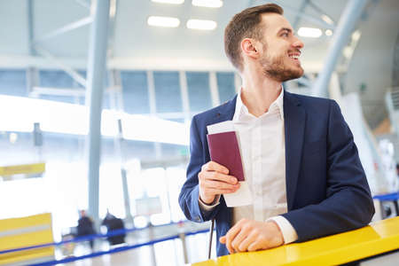 Business man in airport terminal on business trip while changing with passport