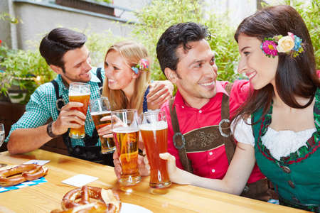 Two laughing couples drink beer together in the beer garden