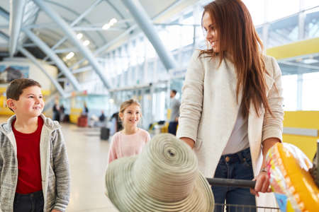 Mother with two children and luggage in the airport terminal are looking forward to the holiday trip