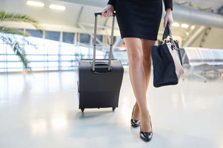 Businesswoman traveling with trolley carrying elegant shoes and bag Archivio Fotografico