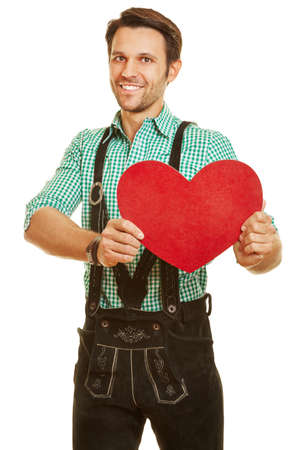 Smiling man in leather pants holds a big red heart