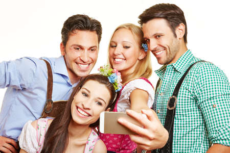 Four happy friends in Bavarian costume take pictures with smartphone Archivio Fotografico