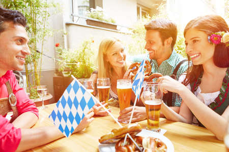 Laughing friends have fun together in the beer garden in Bavaria Standard-Bild