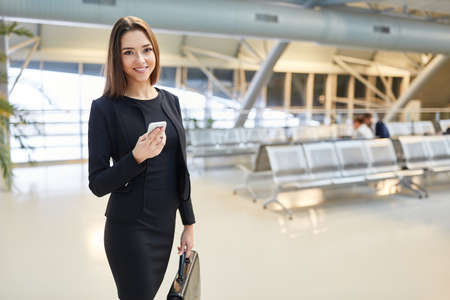 Young successful business woman on mission with smartphone in airport terminal